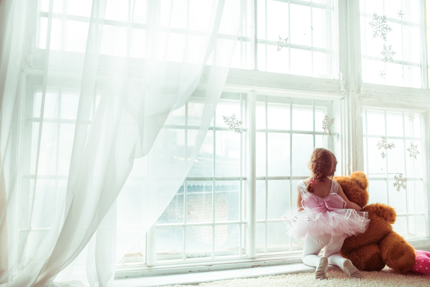 Girl in dancer's suit sits with toy bear before the window