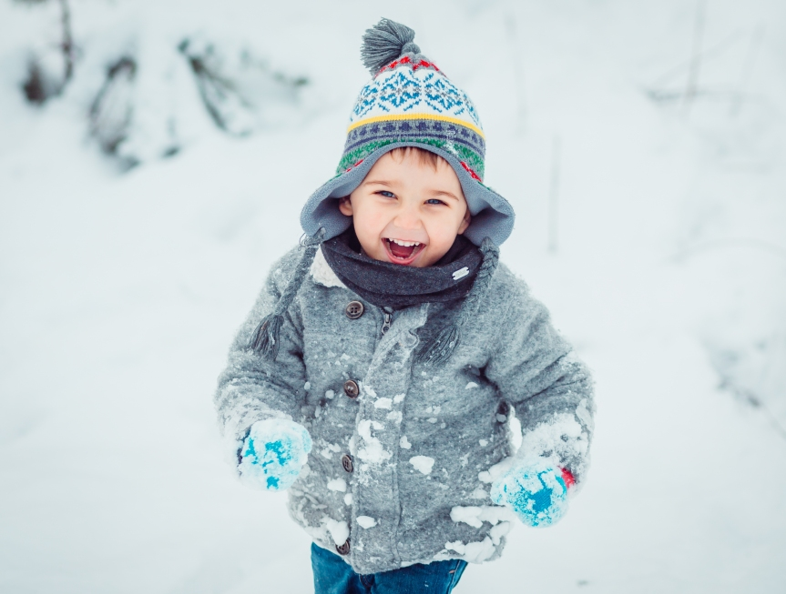 The small child running along snow